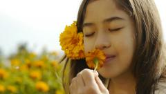 Beautiful Asian Girl Wearing A Flower Smells A Flower And Smiles For The Camera Stock Footage
