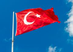 waving flag of turkey over blue sky background - stock photo