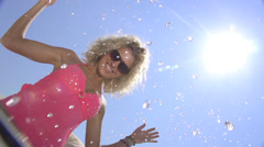 SLOW MOTION: Cheerful woman splashing water into the camera Stock Footage
