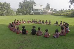 Pre primary students doing exercise on ground, india Stock Photos