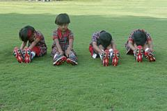 pre primary students doing exercise on ground, india - stock photo