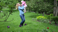 Mother walking daughter in garden blossoming takes child in arms Stock Footage