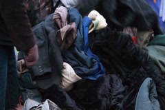 Poor people choosing second hand clothes winter outdoors, click for HD - stock footage