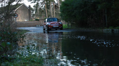Mini Cooper drives through English flood waters (dolly) Stock Footage