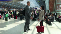 Time lapse business people meet and shake hands at a busy railway station. - stock footage