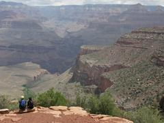 Two Hikers Sit Overlooking The Grand Canyon - stock photo