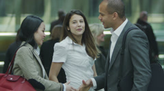 Businessman and businesswoman meet and shake hands at a busy railway station. Stock Footage