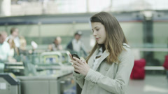 Young woman at a railway station checks her phone as she waits for a train Stock Footage
