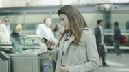 Stock Video Footage of Young woman at a railway station checks her phone as she waits for a train