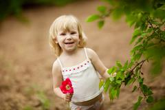 happy small girl with tulip outdoors in sunny day - stock photo