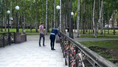 Amorous couple is considering Love Locks on a bridge. - stock footage