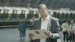 Businessman at a railway station reads the newspaper as he waits for his train - stock footage