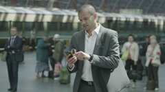 Cheerful businessman waiting for train gets a text message which makes him smile - stock footage