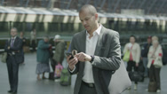 Stock Video Footage of Cheerful businessman waiting for train gets a text message which makes him smile
