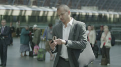 Cheerful businessman waiting for train gets a text message which makes him smile Stock Footage