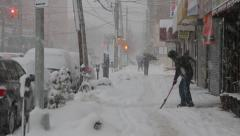 A man plowing street sidewalk in blizzard snow Stock Footage