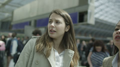 2 young women at a railway station. One is giving the other directions. - stock footage