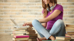 Beautiful girl wearing headset sitting on floor using laptop holding credit card Stock Footage