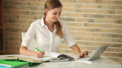 Cheerful girl sitting at desk writing in workbook using laptop and smiling  Stock Footage
