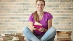Pretty girl wearing earphones sitting on floor reading book looking at camera Stock Footage