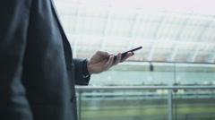 Liikemies katselin hänen puhelimen, kun hän kävelee kiireisen rautatieasema. Arkistovideo