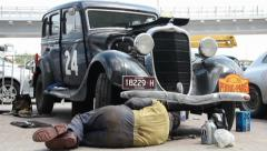 Dodge DR Special, 1934, repair man changing oil under vehicle, click for HD - stock footage