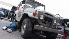 Toyota Landcruiser FJ40, 1960 from Brazil, repairman under car, click for HD Stock Footage