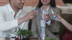 Cheerful group of friends at a restaurant raise their glasses for a toast - stock footage