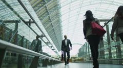 Business people walking through London's St. Pancras railway station. Stock Footage