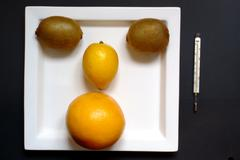 face - orange, kiwi on plate and a clinical thermomete - stock photo