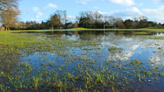 Clouds reflected in flood water on soccer pitch - dolly Stock Footage