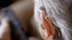 Elderly woman watching TV with hearing aid Stock Footage