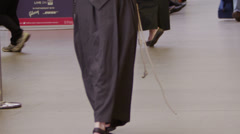 Low angle view of a religious man walking through a busy railway station. Stock Footage