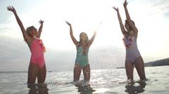 SLOW MOTION: Young women splashing sea water Stock Footage
