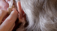 Elderly woman fitting hearing aid - stock footage