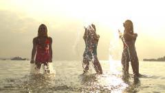 SLOW MOTION: Ladies splashing sea water at sunset Stock Footage