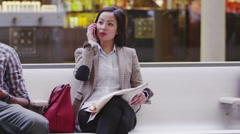 Beautiful asian woman talking on the phone in a busy public area. - stock footage