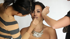 Model Getting Her Hair and Makeup Done Against a White Background - stock footage