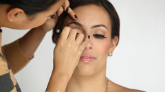 Model Getting Her Makeup Done Against a White Background Stock Footage