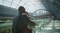 Businessman makes a phone call as he walks through iconic London railway station - stock footage