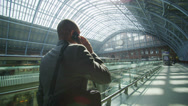 Stock Video Footage of Businessman makes a phone call as he walks through iconic London railway station