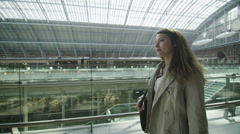 Beautiful woman traveling alone walks through iconic London railway station - stock footage