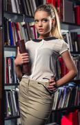 elegant beautiful female student at the library - stock photo