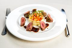 Roasted lamb fillet with potato and olive puree Stock Photos