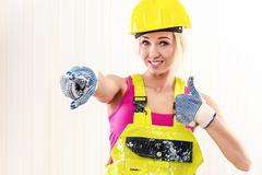 woman in coverall and hard hat showing thumbs up indoors - stock photo