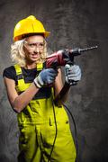 attractive builder woman with a drill in her hands - stock photo