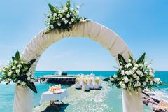 wedding arch and wedding chairs on the empty beach - stock photo