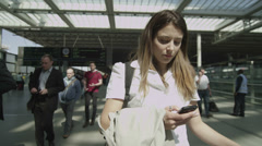 Young woman looking at her phone as she stands in London's St. Pancras railway s Stock Footage