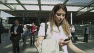 Stock Video Footage of Young woman looking at her phone as she stands in London's St. Pancras railway s