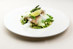 Sea bass fillet with asparagus infused with sauce foam Stock Photos